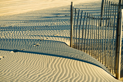 Outer Banks, North Carolina.  Graphic composition of dune fence, light, shadow and repeating ripples in the sand.