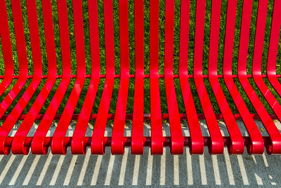 USA, Grand Haven, MI.  Abstract of a red metal slatted bench with shadows.