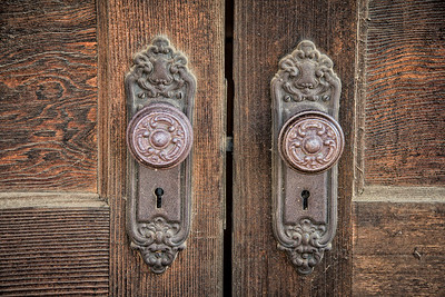 Washington, USA., St. Johns.  Close-up of wooden door and ornate door knobs in the Palouse region.