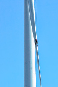 Repair of a wind turbine showing male person on blade.