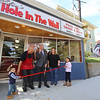 Justine Achin and fiance Eliu Olmo of Lowell open a restaurant, Eliu's Hole in the Wall, in the former Quality Doughnuts building at 398 Fletcher Street. Eliu Olmo and Justine Achin, with son Mateo Olmo, 2, and daughter Gabriella  Olmo, 6, holding the ribbon, hold a ribbon-cutting with Lowell mayor Edward Kennedy. At right, Eliu's aunt, Milagros Olmo Batista, photograpsh the event. She lives in Canovanas, Puerto Rico, and came up as a surprise for the opening. (SUN/Julia Malakie)