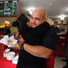 Justine Achin and fiance Eliu Olmo of Lowell open a restaurant, Eliu's Hole in the Wall, in the former Quality Doughnuts building at 398 Fletcher Street. Eliu Olmo hugs his cousin, Keila Matias of Lowell, at the opening. (SUN/Julia Malakie)