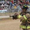 JOHN KLINE | THE GOSHEN NEWS<br /> Jeremy Krezel, with the Goshen Fire Department, sprays water from a fire hose at a target during the Firefighter Challenge at the Elkhart County 4-H Fair grandstand Saturday.