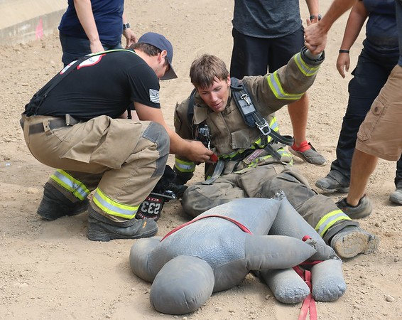 JOHN KLINE | THE GOSHEN NEWS<br /> Karl Lehman, with the Millersburg-Clinton Fire Territory, gets some help removing his fire gear after successfully finishing the Firefighter Challenge at the Elkhart County 4-H Fair grandstand Saturday.