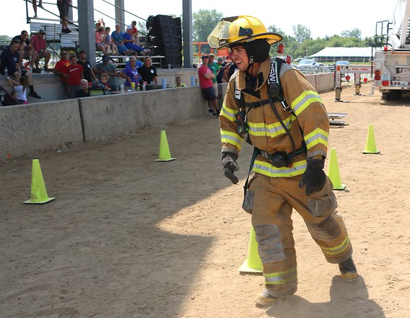 JOHN KLINE | THE GOSHEN NEWS<br /> Sean Dailey, with the New Paris Fire Department, weaves his way through several cones during the Firefighter Challenge at the Elkhart County 4-H Fair grandstand Saturday.