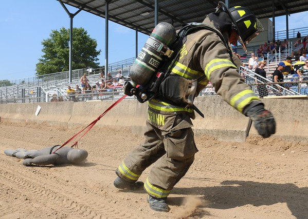 JOHN KLINE | THE GOSHEN NEWS<br /> Phil Grann, with the New Paris Fire Department, drags a 165-pound dummy to the finish line during the Firefighter Challenge at the Elkhart County 4-H Fair grandstand Saturday.
