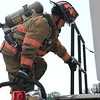 JOHN KLINE | THE GOSHEN NEWS<br /> P.J. Metzler, with the Benton Township Volunteer Fire Department, climbs down off of a fire truck during the Firefighter Challenge at the Elkhart County 4-H Fair grandstand Saturday.