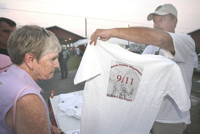081106 SCF-911 shirts 2 Staff photo by Joe Kmetz Carneys Point Fireman Frank Walker, right, sells a shirt to Evelyn Shuman of Salem. The Salem County Remembers 9-11 Remembrance Ceremony shirts were sold at the Salem County Fair in Pilesgrove on Thursday. Proceeds will benefit the Sept. 11 Commemoration event that will be held at the fairgrounds on Sept. 11. Carneys Point Fire and Police are the hosts of the event this year.