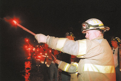 9/17/01Vigil1 Staff photo by Joe Kmetz Carneys Point Fire Chief Edward Micallef and a host of County firefighters hold flares at Sunday night's vigil at the waterfront in Penns Grove. Later all the flares were thrown into the Delaware River.