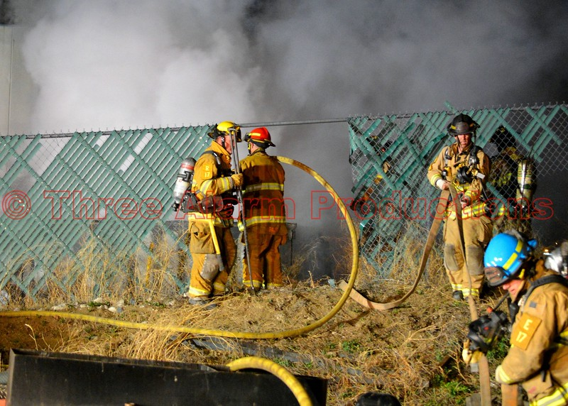 Colorado Springs Firefighters working a well involved trailer fire, near a commercial building. April 9, 2015
