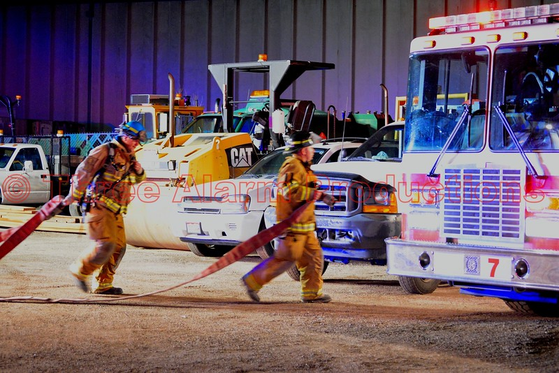 Colorado Springs Firefighters working to hook a supply line up to CSFD Fire Engine 7, on the scene of a well involved trailer fire, next to a commercial building. April 9, 2015