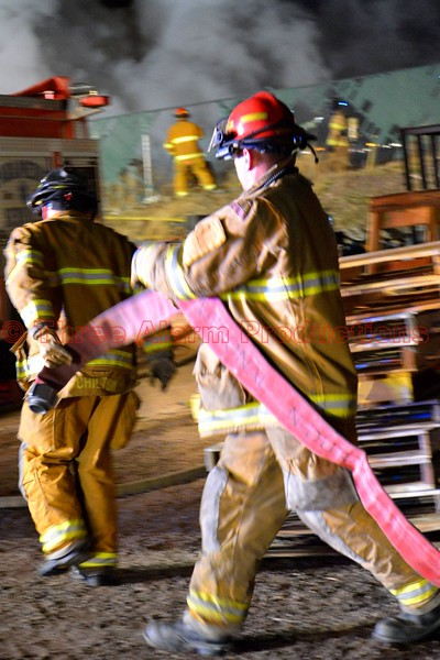 Firefighters working to get Colorado Springs Fire Engine 7 a water supply from a hydrant, to bring a well involved trailer fire under control. April 9, 2015