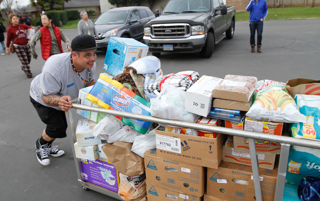 . Volunteers push a cart of supplies into the Fairgrounds Monday February 13, 2017 at the Silver Dollar Fairgrounds in Chico, California. About 700 people currently occupy the shelter as an emergency evacuation was called Sunday evening on the town of Oroville and surrounding areas displaying over 180,000 people. (Emily Bertolino -- Enterprise-Record)