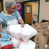Emily MacRae executive director of North Central Faith Based Community Coalition works on getting the meals ready for all the people in need she was feeding on Wednesday night at the YMCA in Fitchburg. SENTINEL & ENTERPRISE/JOHN LOVE