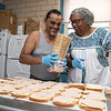 Emily MacRae executive director of North Central Faith Based Community Coalition works has a good laugh with Assistant Food Manager Louie Martinez as they get food ready for the many they help feed out of the YMCA in Fitchburg on Wednesday night SENTINEL & ENTERPRISE/JOHN LOVE