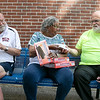 Emily MacRae executive director of North Central Faith Based Community Coalition, center, hands out ice cream sandwiches to the people in line waiting to get a meal from her group at the YMCA in Fitchburg on Wednesday night. From left is Peter Carkin, MacRae and Ed Daniels. SENTINEL & ENTERPRISE/JOHN LOVE