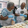 Emily MacRae executive director of North Central Faith Based Community Coalition works with Line Cook Ronald Logos as they get food ready for the many they help feed out of the YMCA in Fitchburg on Wednesday night SENTINEL & ENTERPRISE/JOHN LOVE