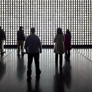 Slowly, a dim light begins to emanate from the front wall, progressively growing stronger, its white rays filtering through seemingly endless rows and columns of silhouettes. (Courtesy Alfredo Jaar Studio)