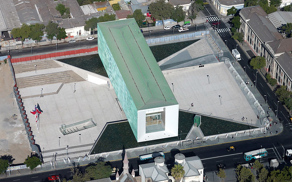 "Architectural Rendering - Aerial view of an architectural rendering that features Museo de la Memoria y Los Derechos Humanos and Plaza de la Memoria (Museum of Memory and Human Rights and The Plaza of Memory) The large blue-green rectangular building is the main edifice of the museum, it is three stories high and surrounded by glass walls. The north and south walls are laminated in copper, which according to the museum's website, ""emphasizes national identity."" To the left of the building, embedded in the ground at a slight angle, is the entrance to the memorial, La geometria de la conciencia (The Geometry of Consciousness). (Courtesy Alfredo Jaar Studio, Translation by Lissette Olivares)"