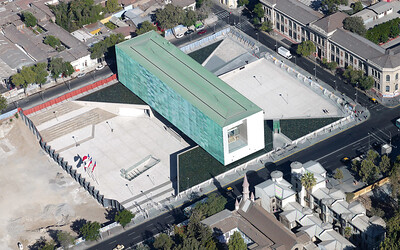 "Architectural Rendering - Aerial view of an architectural rendering that features Museo de la Memoria and Plaza de la Memoria –  The large blue-green rectangular building is the main edifice of the museum, it is three stories high and surrounded by glass walls. The north and south walls are laminated in copper, which according to the museum's website, ""emphasizes national identity."" The museum was designed by an architectural team from Sao Paulo that includes Mario Figueroa, Lucas Fehr and Carlos Dias. On the north side of the building, embedded in the ground at a slight angle, is the entrance to the memorial Geometría de la conciencia (The Geometry of Consciousness) (Courtesy Alfredo Jaar Studio, Translation by Lissette Olivares)"
