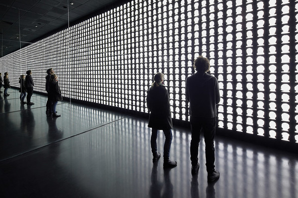 Two lateral walls of mirrors create the effect of infinite reflection- of both the memorial's visitors and its lighted silhouettes. (Courtesy Alfredo Jaar Studio)