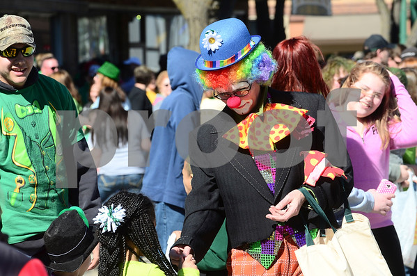-Messenger photo by Jesse Major<br /> <br /> Jackie Vannoosbree, dressed as a clown, hands out candy to children at the St. Patrick's Day parade in Emmetsburg Saturday.