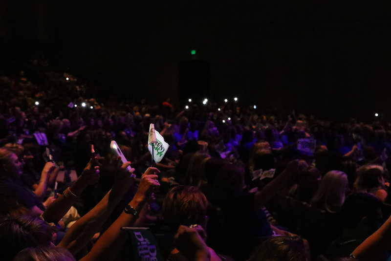 Crowd waves phone lights during song.
