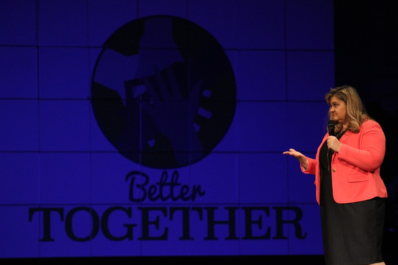 School board president Julie Cole stands in front of the Better Together logo.