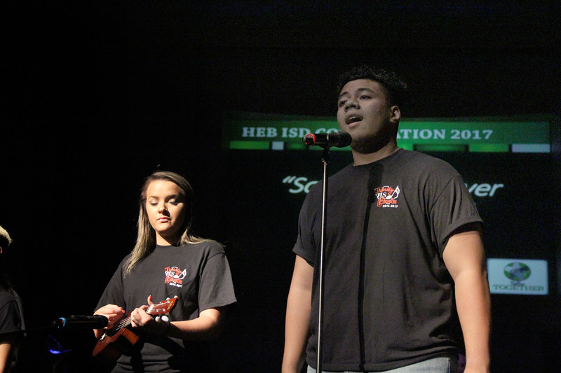 High school choir students perform a song, playing the ukulele.