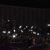 Audience shine phone lights in rhythm to the music.