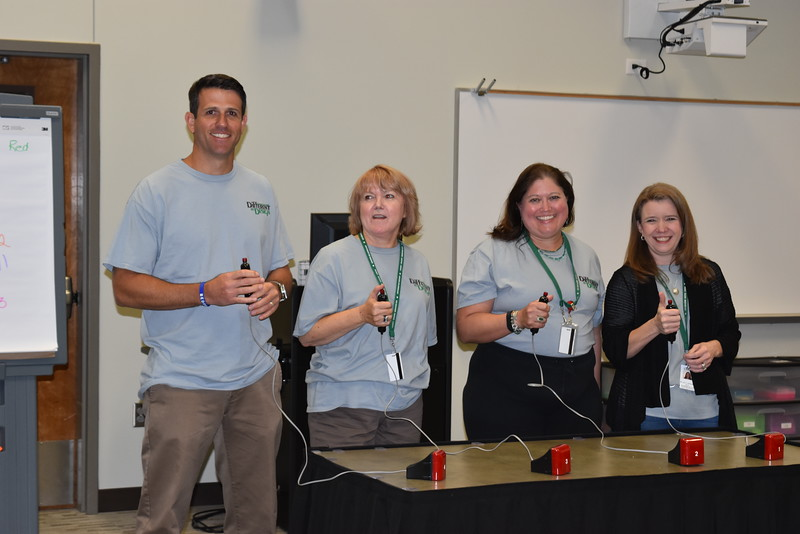 Administrators play a game with buzzers.