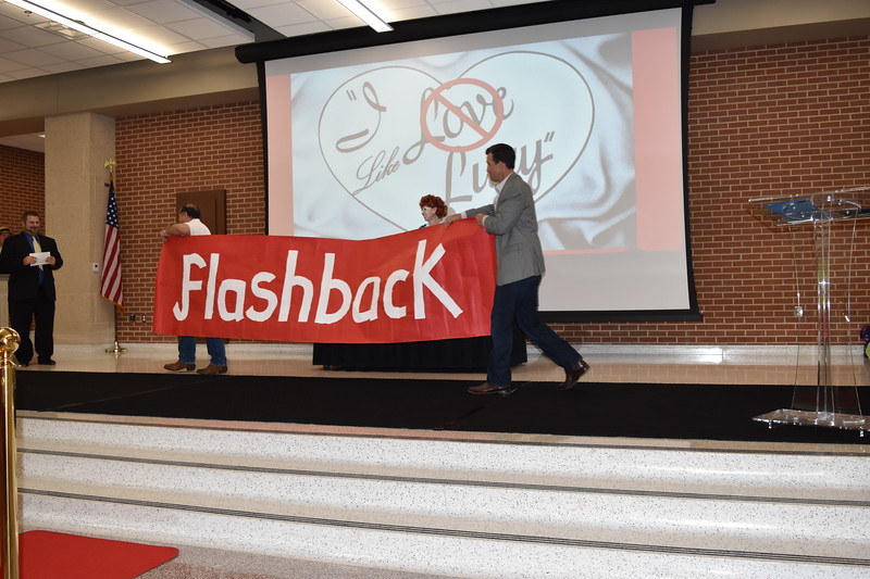 "District administrators perform a skit, carrying a large banner that says ""Flashback""."
