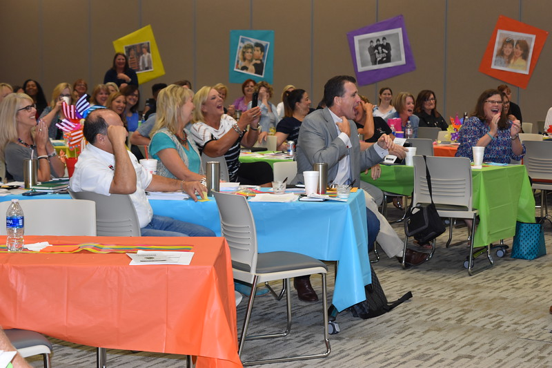 School district administrators show their amusement by laughing and applauding.
