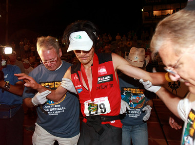 Japanese runner Tsuyoshi Kaburagi is helped to the scale at the finish line.  Kaburagi was a surprise second finisher, running the WS100 for the first time.