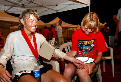 Anita Ortiz has her blood pressure and pulse checked by a medical aid station worker upon winning the women's division.