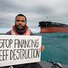 30 aniversario hundimiento Rainbow Warrior. Activista muestra pancarta para proteger la Gran Barrera de Coral