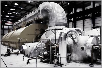 1 GIGAWATT  .das ist eine Milliarde Watt, also fast 1,4 Millionen PS Stromleistung. Soviel erzeugt der Generator des Blocks K des Braunkohlekraftwerks Niederaußem. Der Generator selbst ist hier gar nicht zu sehen, der liegt hinter den gelben Niedrigdruckturbinen.  Vorne rechts, im hellen Bereich kommt der Sattdampf an, mit 576 °C und 265 bar. Dann wird die in ihm enthaltene nutzbare Energie (die sogenannte Exergie) zu weit über 90% abgearbeitet, d.h. in Strom verwandelt, um schließlich die NIedrigdruckturbinen mit schlappen 30 Millibar und 27°C zu verlassen.  Dann, im Konsdensator, wird dieser merkwürdige Schlapp-Dampf mit dem aus dem höchsten Kühlturm der Welt kommenden Kühlwasser auf ca. 17°C abgekühlt - das reicht aus, damit er wieder zu Wasser wird und bereit ist, für eine neue Runde durch den Dampferzeuger.