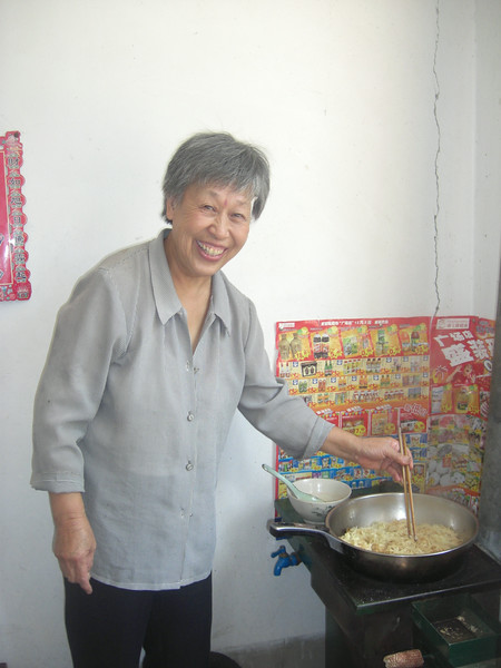 Ms. Liang was cooking noodles with new biomass stove. April 2010.