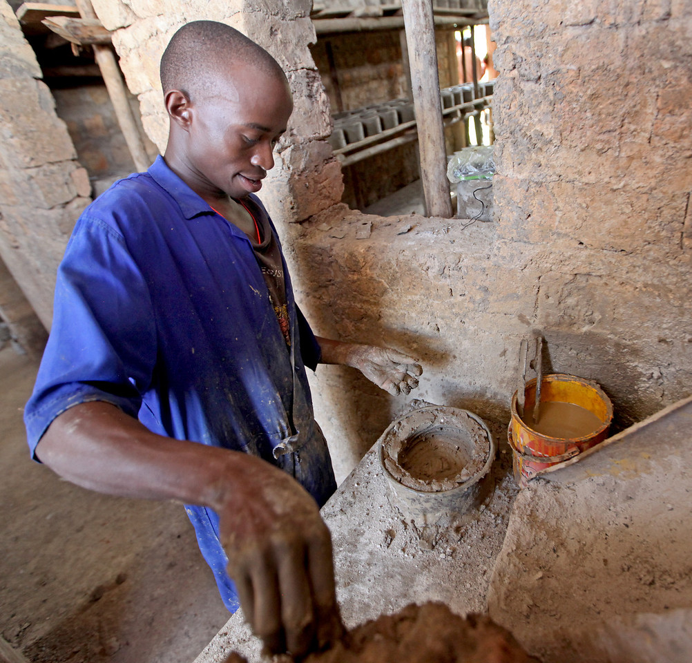 Peter Mutyaba molds a liner for a high efficiency charcoal cookstove  at EUF's factory in Kawempe, a division ofKampala, Uganda. The clay liner is the heart of an efficient stove and responsible for the energy savings over a traditional inefficient stove.