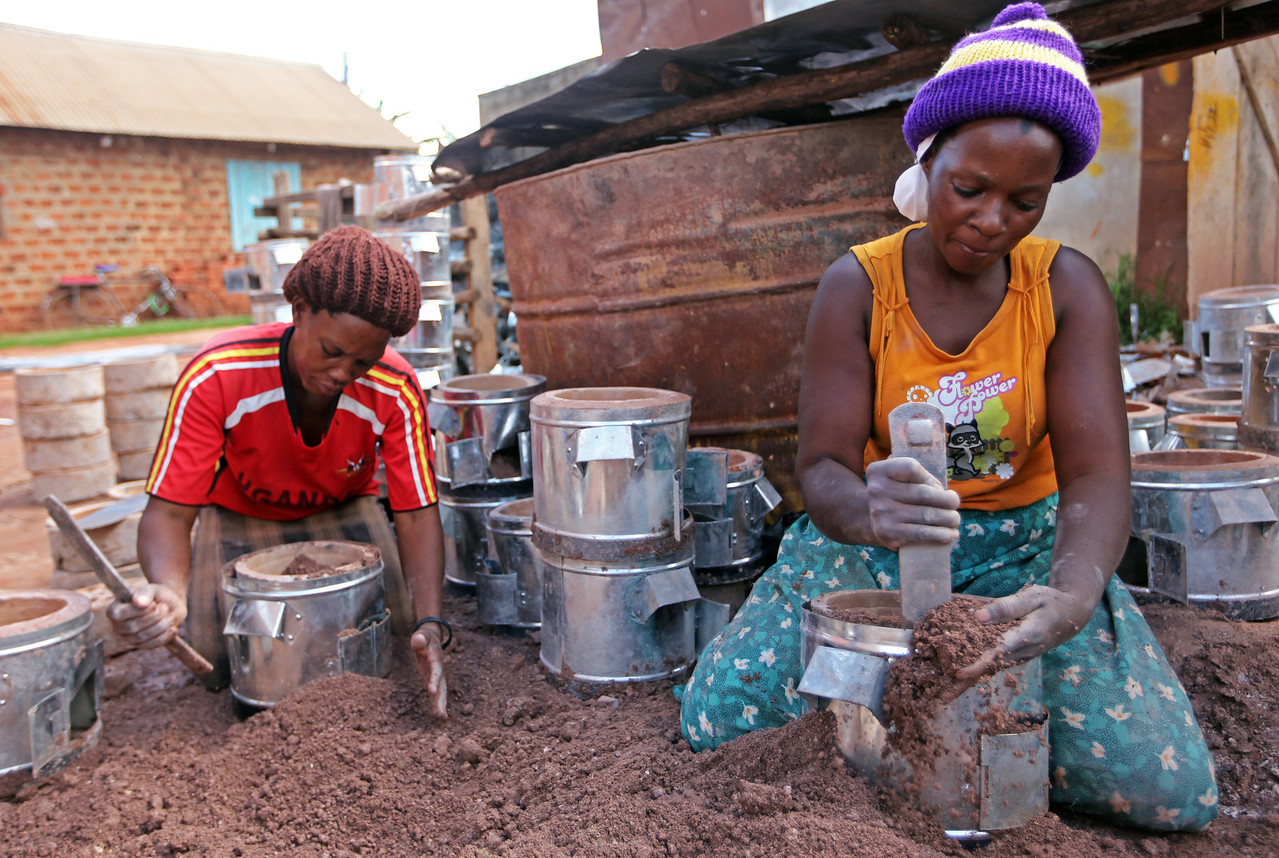 Nakaba Jaliya, left, and Zam Namuga use a mixture of clay, mica, and cement to secure liners inside the metal stove cladding, one of the final steps of producing an energy efficient charcoal cookstove.