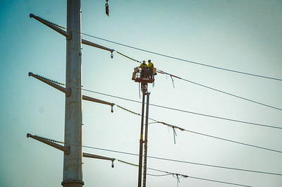 Electricians work on a power line at the intersection of Hwy 470 and Pryor Road in Lee's Summit in March 2021.