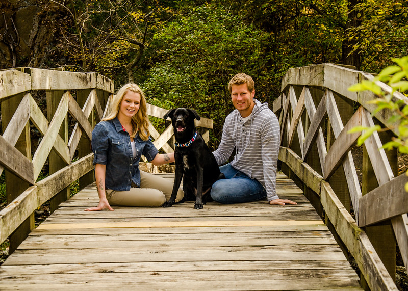 engagement photo of couple sitting on wooden bridge