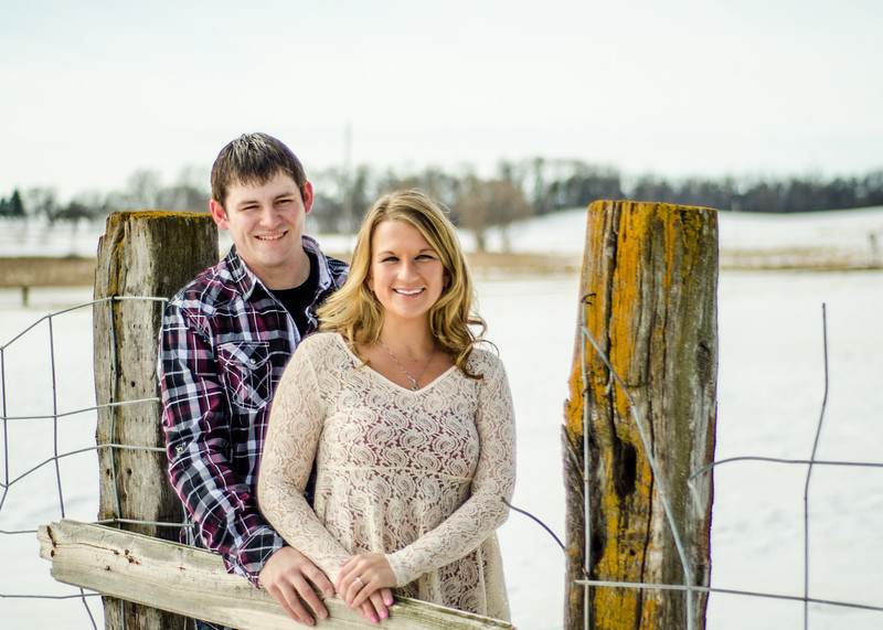 Engagement photo of couple standing in front of wire fence
