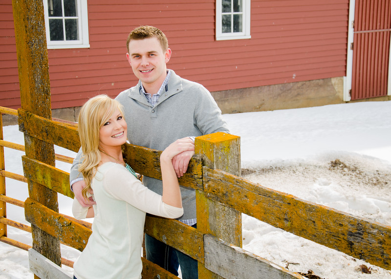 Engagement photo of couple on wooden fence
