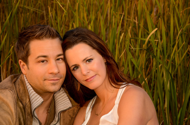 Engagement photo of couple sitting in front of lake grass