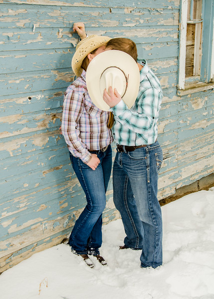 engagement photo of couple kissing behind hat