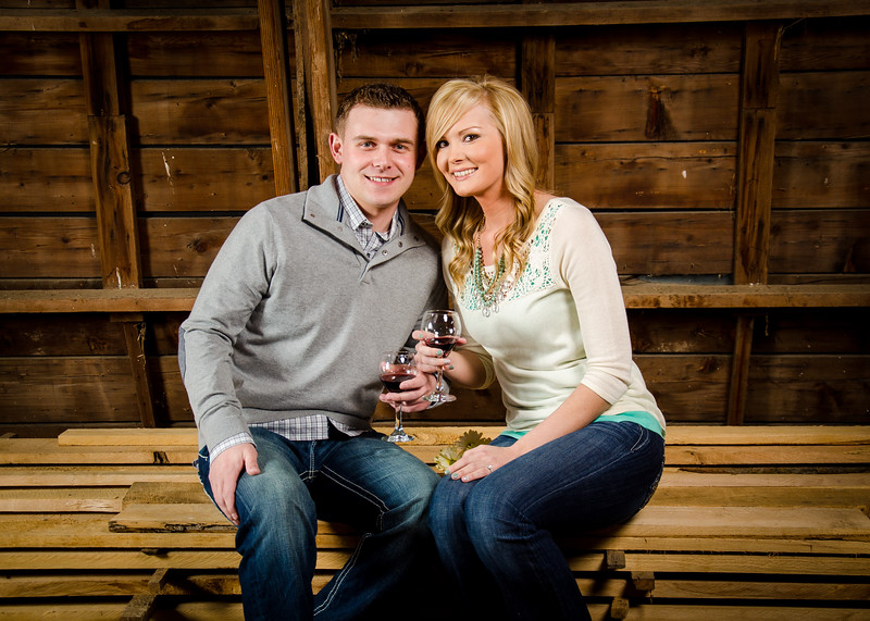engagement photo of couple sitting on lumber in barn