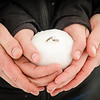 engagement photo of couple holding engagement ring in snowball
