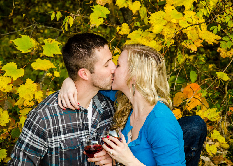Engagement photo of couple kissing in front of fall leaves