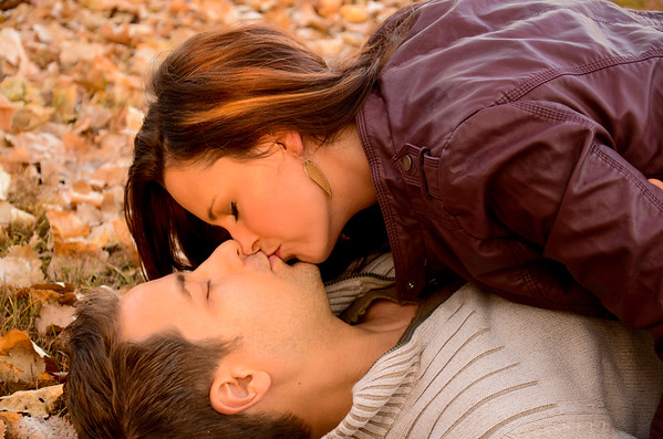 Engagement photo of couple kissing in the fall leaves
